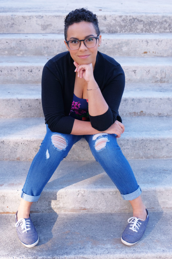 A photo of Allie, a young woman of mixed race, with short curly hair and glasses, sitting on some stairs with her fist under her chin.