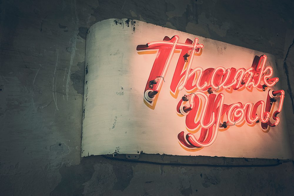 "A red neon sign that says ""Thank you!"""