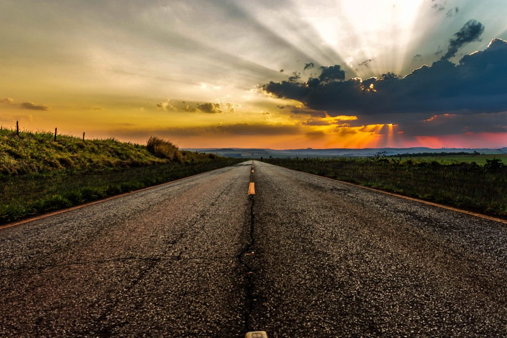 An image of a stunning sunset over some mountains and fields but the main focus of the image is the paved road that stretches on toward the horizon