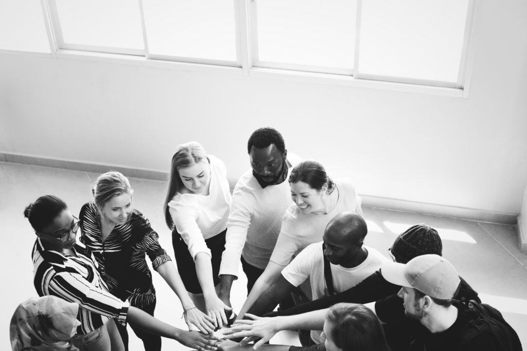 A black and white image of a group of people - black white male and female - putting their hands in as a team